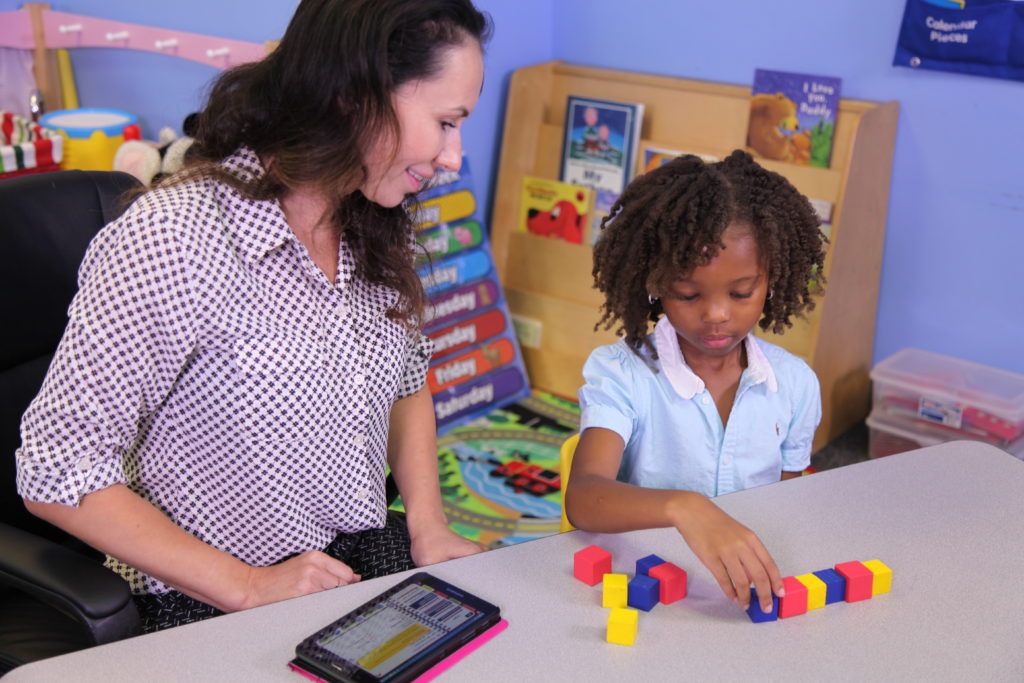 Special Needs Student and Teacher using colored blocks in a one-on-one lesson