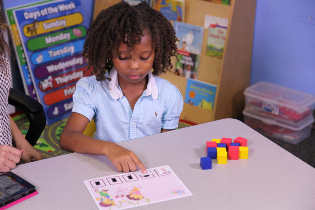 Special needs girl pointing to shapes on a page in a one-on-one lesson